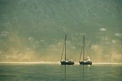 Boote auf Meer mit Häusern auf Hintergrund Stockfotografie