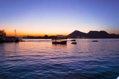 Boote auf pichola See an der Dämmerung mit Bergen im Abstand Lizenzfreies Stockbild