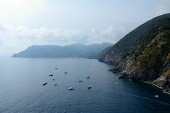Boote in der Bucht und hohe Klippe in Vernazza, Italien Lizenzfreies Stockfoto