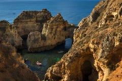 Boote in der kleinen Bucht zwischen den Sandsteinklippen beim Ponta DA Piedade in Lagos, Portugal Stockfotos