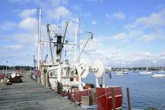 Boote der kommerziellen Fischerei durch ein hölzernes Dock Stockbilder