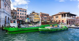 Boote, die Abfall durch Kran auf Grand Canal am Railto-Markt in Venedig, Italien sammeln stockfoto