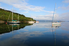 Boote, die auf einem ruhigen Meer anlegen Stockbild