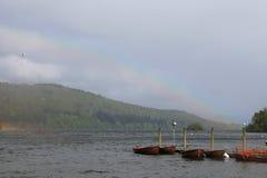 Boote, die auf See-Bezirk, England, Regenbogen im Hintergrund ankoppeln Lizenzfreies Stockbild