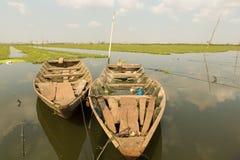 Boote, die nahe Reisfeldern mit Phnom Penh im backgroun schwimmen Stockfotografie