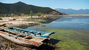 Boote durch das flache Ufer von Lugu See lizenzfreies stockfoto