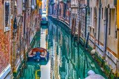 Boote in einem schmalen Kanal in Venedig Lizenzfreies Stockfoto