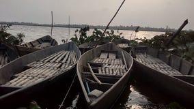 3 Boote fließen auf die Bank des Flusses in die Sonnenuntergangzeit Stockfotografie