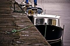 Boote gebunden an einem Steindock Stockfoto