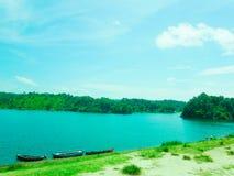 Boote im blauen Seewasser und in den grünen Hügeln außerdem stockfotografie
