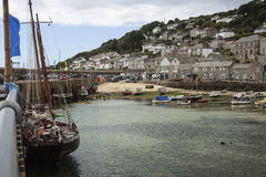 Boote im Hafen am Mousehole, Cornwall bei Ebbe Stockfotos