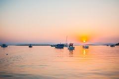 Boote im Meer bei Sonnenuntergang im Sommer mit Bergen auf backgroun Lizenzfreies Stockbild