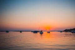 Boote im Meer bei Sonnenuntergang im Sommer mit Bergen auf backgroun Lizenzfreie Stockfotografie