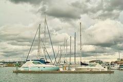 Boote im Moorage gegen Wolken Stockbilder