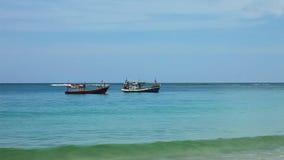 Boote im tropischen Meer nahe tropischem Strand stock footage