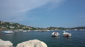 Boote im Villefranche-sur-Mer und Felsen auf dem Vordergrund stock footage
