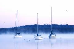 Boote im Wasser auf kaltem nebeligem Morgen Stockfotos