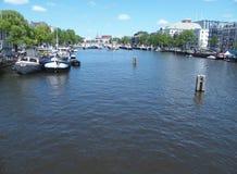 Boote in Kanal gracht bereit zu kreuzen und traditionelle Häuser in Amsterdam lizenzfreies stockfoto