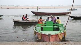 Boote mit Leuten segeln durch den Ganges nahe bei einem Boot, das in der Bucht steht stock video