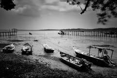 5 Boote, 2 Piers und 1 Bestimmungsort. Stockfotos