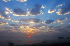 Boote und drastische Wolken während des nebeligen Sonnenaufgangs Stockfotos