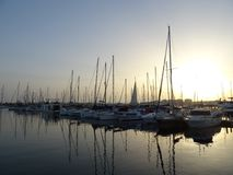 Boote und ihre Reflexion auf Wasser Sonnenuntergang in Torrevieja stockfotografie