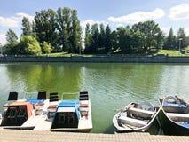 Boote und Katamaran auf einem Teichsee in einem Flusskanal mit grünem geblühtem Wasser werden auf dem Ufer festgemacht stockfoto