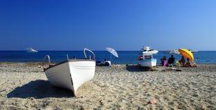 Boote und Leute auf dem Strand Lizenzfreies Stockbild