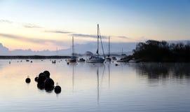 Boote und Nebel des frühen Morgens Stockbilder