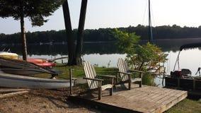 Boote und Sitze durch den See Stockbilder