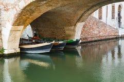 Boote unter Brücke in Comacchio, Italien stockbilder