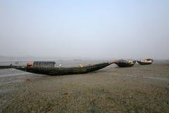 Boote von den Fischern bei Ebbe angeschwemmt im Schlamm auf der Küste des Golfs von Bengalen, Indien Lizenzfreie Stockfotos