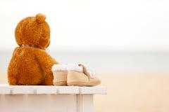 Bootees плюшевого медвежонка и младенца одиночества остаются на sunbed Стоковое Изображение RF