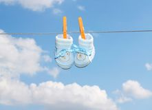 Bootees. Of the child on a cord, against the sky Stock Image