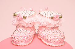 Bootees on christening cake Royalty Free Stock Images