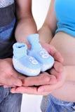 Bootees dei piccoli bambini blu in mani Fotografia Stock