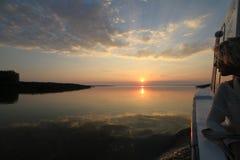 Bootfahrt der jungen Frau bei Sonnenuntergang auf dem Donau-Delta Stockbild