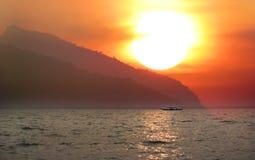 Bootfahrt in einem See während des Sonnenuntergangs Lizenzfreie Stockfotos
