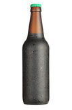 Bootle drops. Isolated bottle of dark beer with cap and drops Royalty Free Stock Images