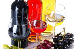Bootles and glasses of wine with black, red and white grapes Royalty Free Stock Images