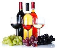 Bootles und Gläser Wein mit den schwarzen, roten und weißen Trauben Lizenzfreie Stockfotografie