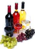 Bootles und Gläser Wein mit den schwarzen, roten und weißen Trauben Lizenzfreie Stockfotos