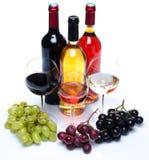 Bootles und Gläser Wein mit den schwarzen, roten und weißen Trauben Stockfotos