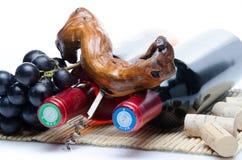 Bootles van wijn met zwarte druiven en een kurketrekker Royalty-vrije Stock Afbeeldingen