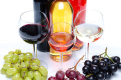 Bootles y vidrios de vino con las uvas negras, rojas y blancas Imagenes de archivo
