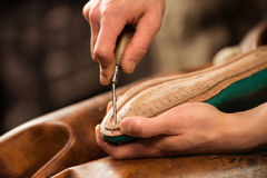 Bootmaker sitting in workshop making shoes. Cropped image of bootmaker sitting in workshop making shoes Royalty Free Stock Photos