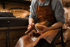 Bootmaker in workshop making shoes. Stock Photos
