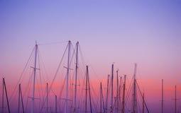 Bootmasten onder een roze en oranje zonsondergang stock fotografie