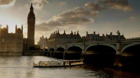 Bootpassen onder de Brug van Westminster bij zonsondergang stock footage