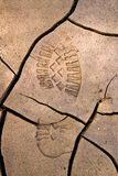 Bootprint in cracked earth. Imprint of a boot in cracked earth stock photos